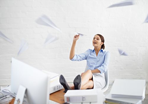 young businesswoman throwing paper planes while sitting at her desk