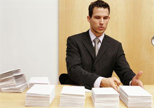 Young businessman stacking envelopes on desk