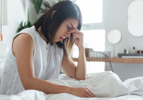 woman in bed with a headache