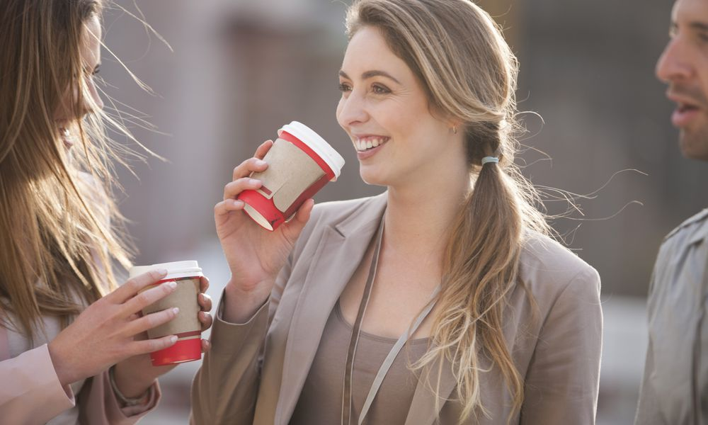 Models pose a business people drinking coffee