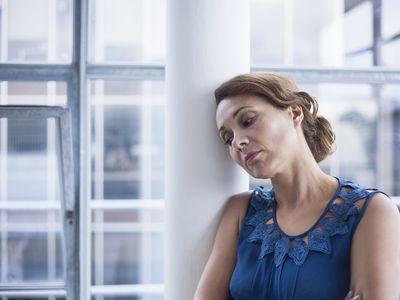 Woman leaning against pillar