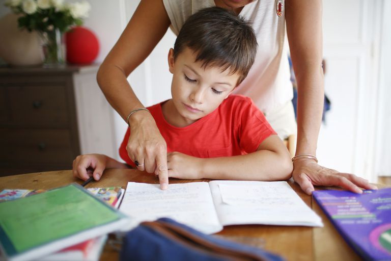 Young boy doing his homework with his mom