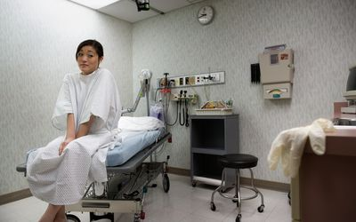 Low angle view of a young Asian woman sitting on an examination table.