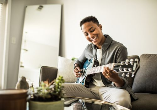 A Black person with short hair is seen with an electric guitar in a well-lit room.