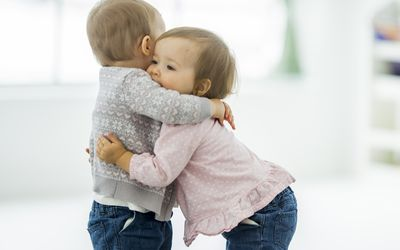 Two twin baby girls are playing together and hugging at daycare