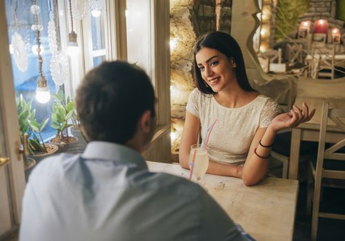 Portrait of smiling young woman talking to her boyfriend in a restaurant