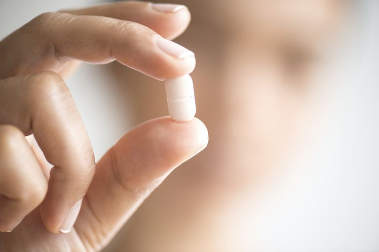 A woman holding a pill