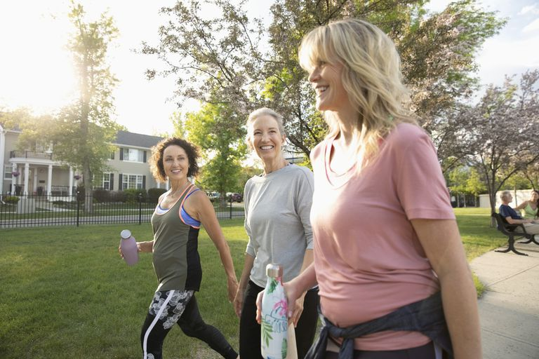 Smiling senior women walking in a sunny park