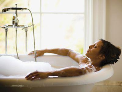 woman meditating in the bathtub