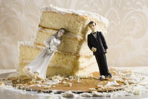 Bride and groom cake topper lean on wedding cake.