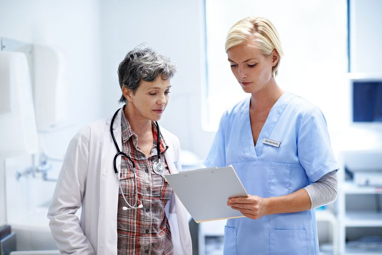 Younger woman in scrubs consults with older doctor