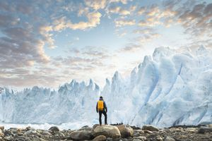 man standing at the base of ice mountains