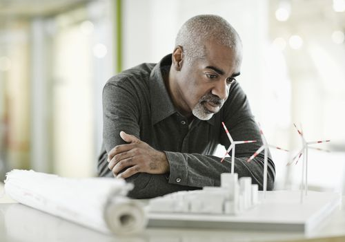 Businessman Examining Wind Power Plant Model