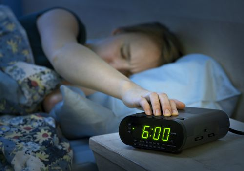 woman hitting snooze on her alarm clock