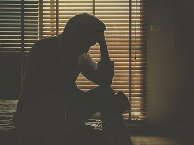 Sad man sitting in dark room