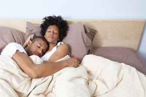 Couple sleeping in bed, embracing