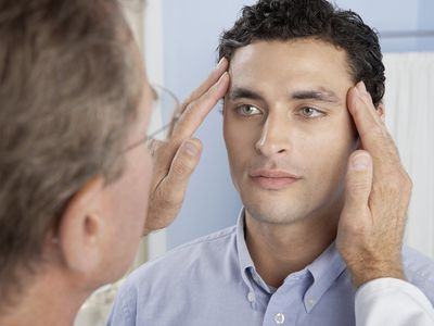 A doctor examines a patient's eyes.