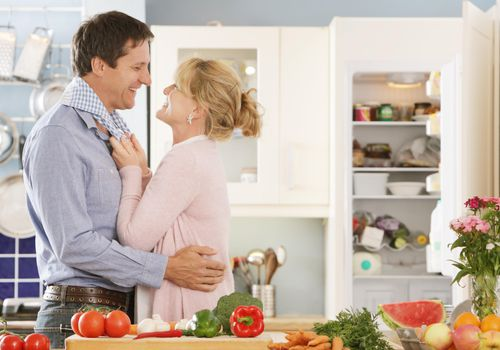 Couple embracing in kitchen whilst preparing meal