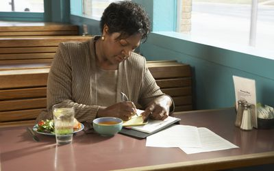Woman sitting at table in diner writing on paper