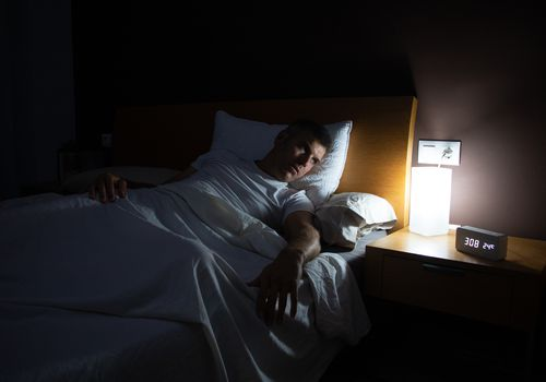 A man with insomnia looks at the clock at dawn from the bed with concern