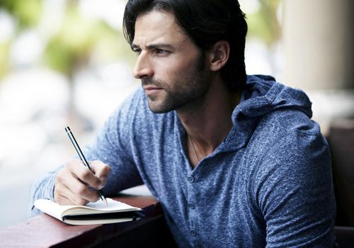 Man writing in a journal outside