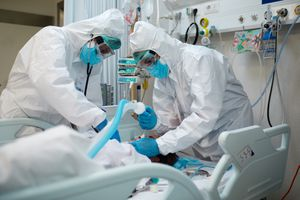 Two doctors wearing head-to-toe protective gear intubate a COVID-19 patient in the intensive care unit.