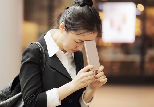 Woman coping with stress while holding phone