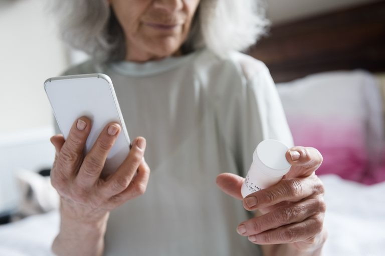 Older woman checking prescription with cell phone