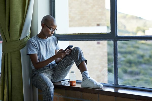 Bald female student text messaging through phone