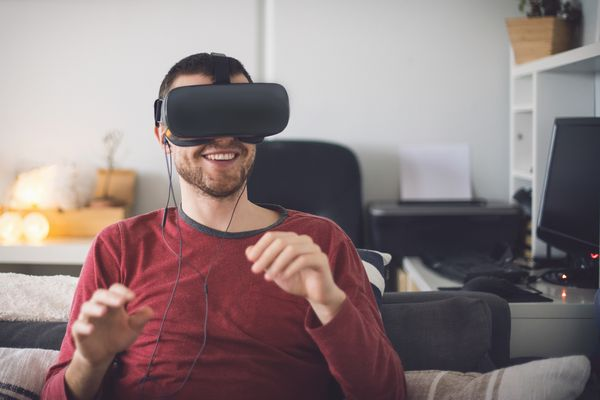 Man using virtual reality headset, sitting on couch
