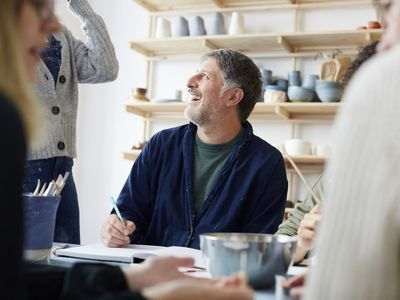 Smiling mature male student talking with female instructor in art studio