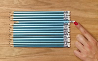 Woman pushing pencil into even line with other pencils