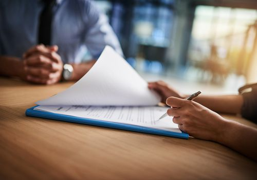 Cropped shot of a man and woman completing paperwork together at a desk