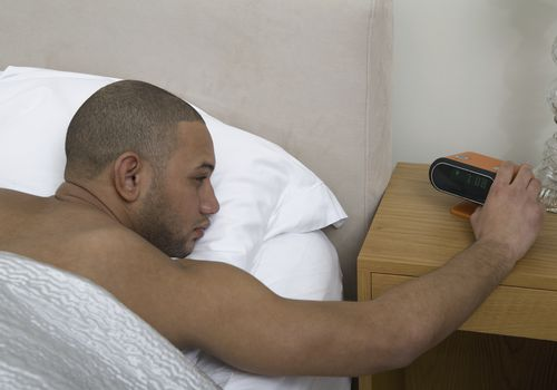 Young man pushing snooze button on alarm clock