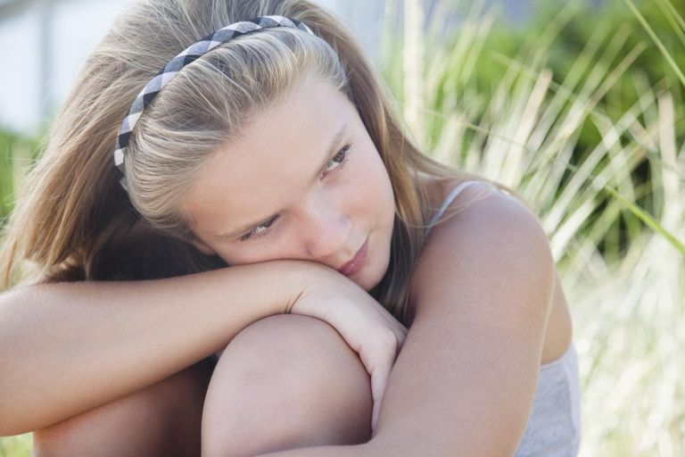 Young girl with hugging her knees at beach