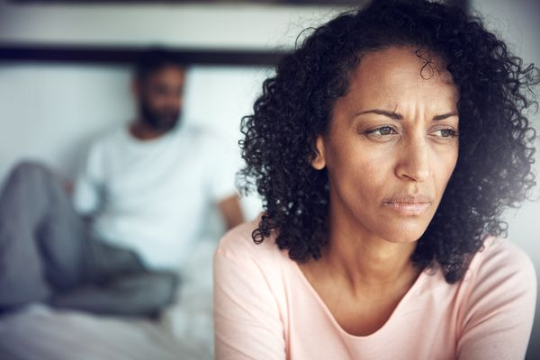 upset woman with man in background