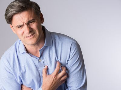 anxious appearing man holding his chest in pain