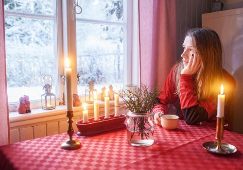 Woman alone at dinner table decorated for Christmas