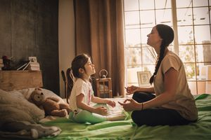 mother and daughter meditating in child's bedroom