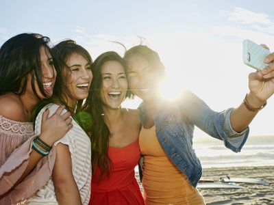 Women taking pictures together on beach