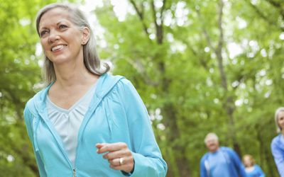 Mature smiling woman walking in a park