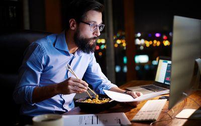 Man multitasking at his desk while working late