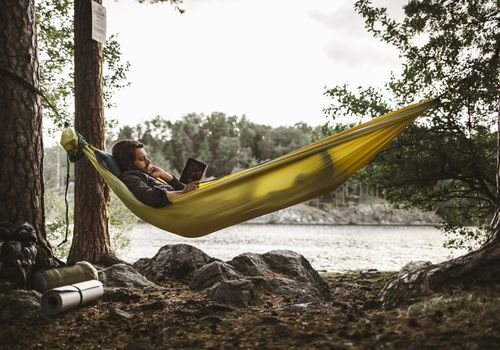 Man reading outdoors in a hammock