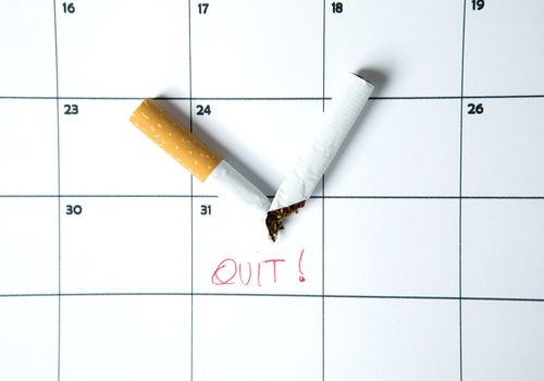 "Cigarette snapped in half on top of a calendar with ""Quit!"" written on it."