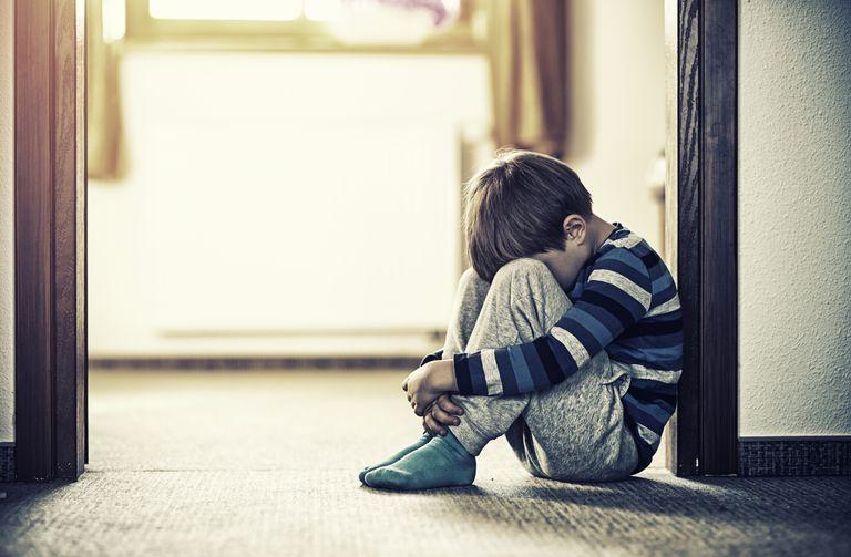 Abused little boy sitting on the floor