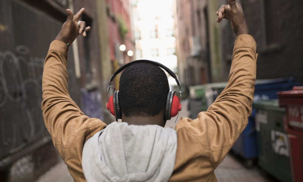 Man with arms raised in urban alley