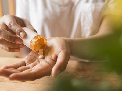 Hands of woman pouring prescription medicine in hand