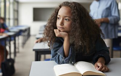 Girl sitting with book and looking thoughtful out of window