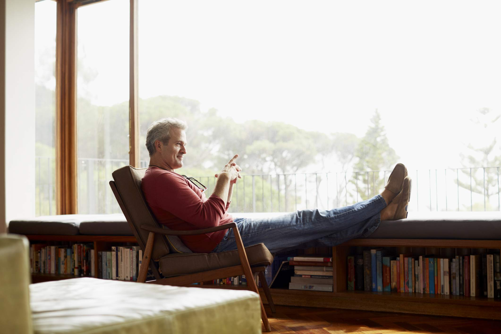 content mature man with feet up looking out at landscape
