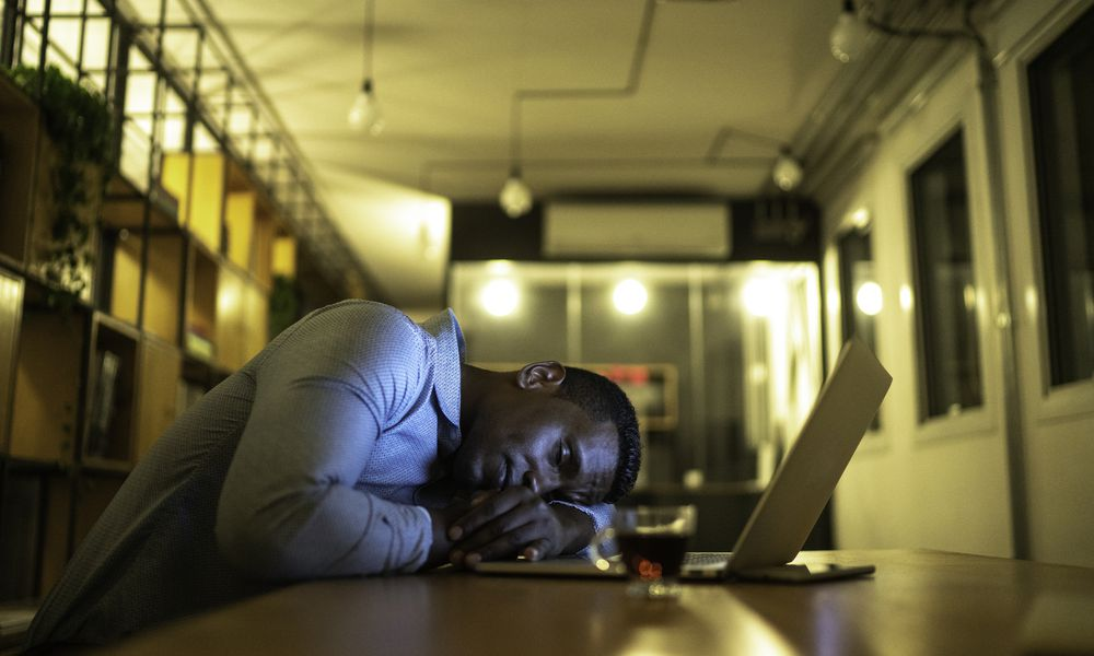 A man asleep at his desk in front of his laptop